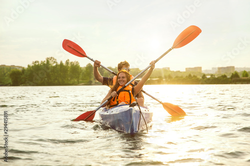 Happy young caucasian couple kayaking on river with sunset in the backgrounds. Having fun in leisure activity. Happy male and female model laughting on the kayak. Sport, relations concept. Colorful. - 294415891