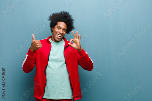 Fotografie, Obraz  young black sports man feeling happy, amazed, satisfied and surprised, showing o