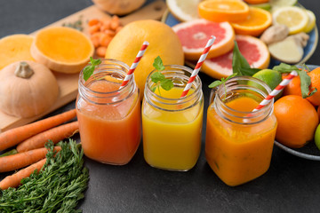 food , healthy eating and vegetarian concept - mason jar glasses of orange and carrot juices with paper straws, fruits and vegetables on slate table