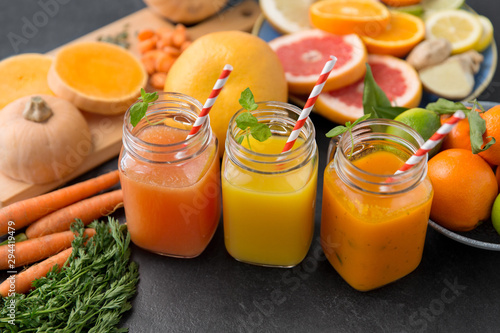 Foto auf AluDibond Natur food , healthy eating and vegetarian concept - mason jar glasses of orange and carrot juices with paper straws, fruits and vegetables on slate table
