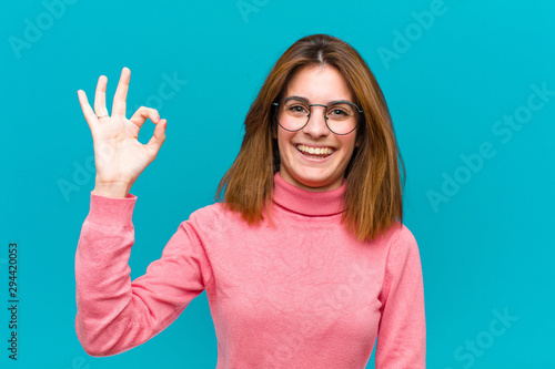 Photo sur Toile Ecole de Danse young pretty woman feeling happy, relaxed and satisfied, showing approval with okay gesture, smiling against blue background