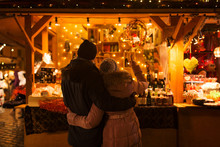 Love, Winter Holidays And People Concept - Happy Senior Couple Hugging At Christmas Market Souvenir Shop Stall In Evening