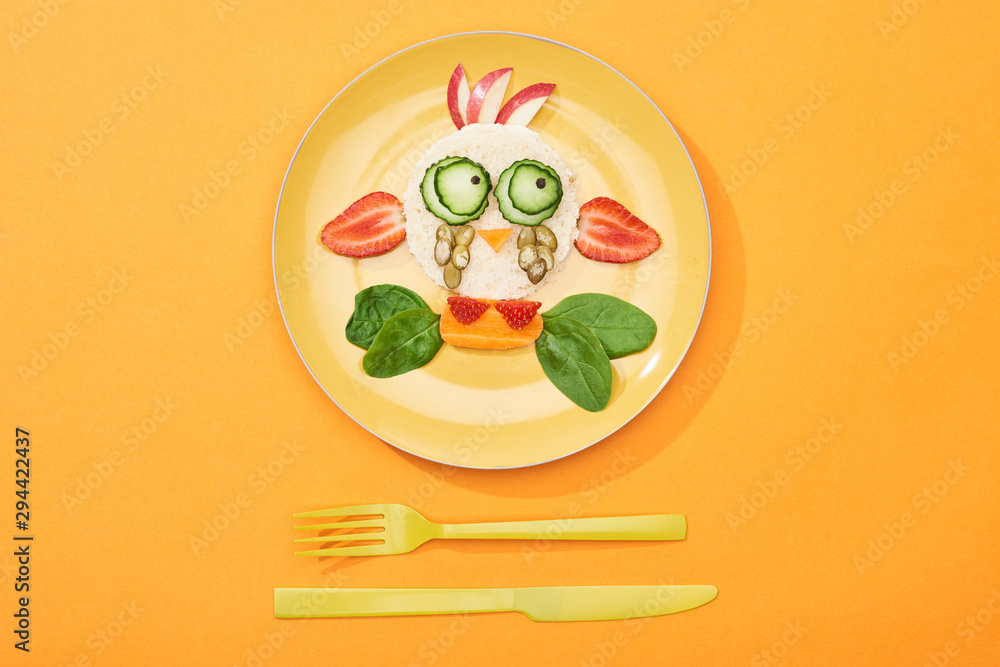 Fototapety, obrazy: top view of plate with fancy cow made of food for childrens breakfast near cutlery on orange background