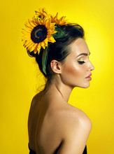 A Beautiful Young Dark-haired Girl With Perfectly Smooth Skin Costs Half A Turn On A Yellow Background. Sunflowers In The Form Of Decorations In The Hair.