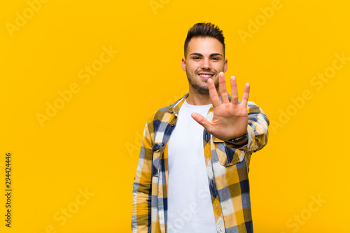 Photo  young hispanic man smiling and looking friendly, showing number five or fifth wi