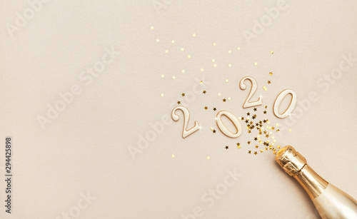 Fotografía  Creative Christmas and New Year composition with golden champagne bottle, confetti stars and 2020 numbers