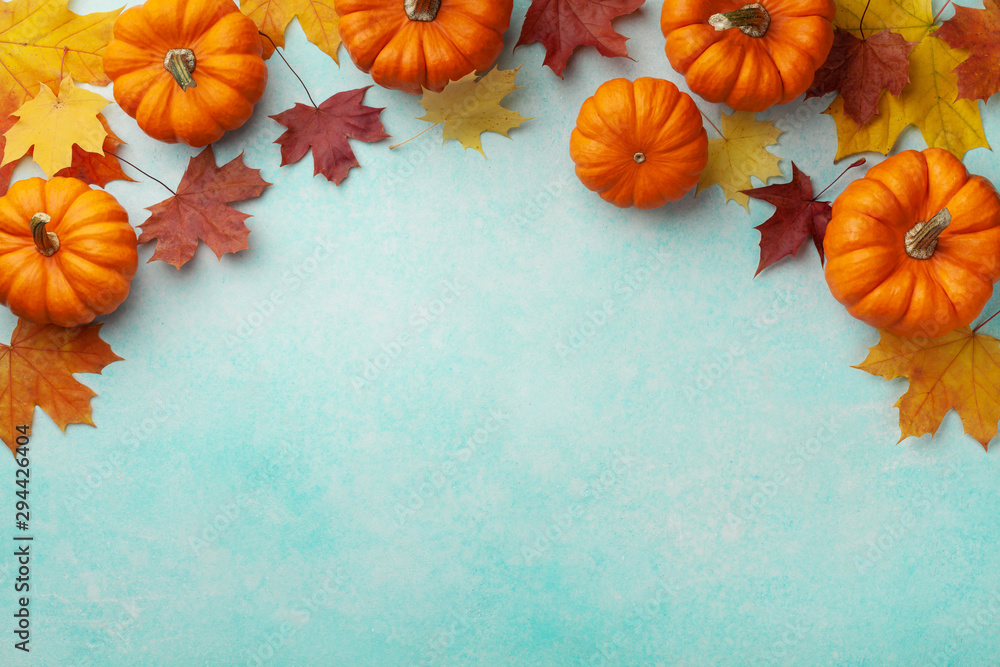Fototapeta Autumn Thanksgiving background. Pumpkins and maple leaves on turquoise table top view.