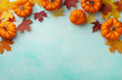 canvas print picture - Autumn Thanksgiving background. Pumpkins and maple leaves on turquoise table top view.