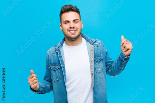 young hispanic man smiling, feeling carefree, relaxed and happy, dancing and listening to music, having fun at a party against blue background - 294426603