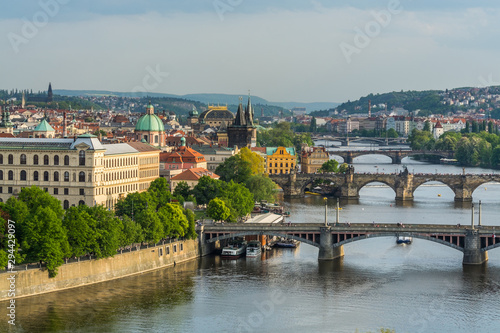 Fototapeta Aerial view of citycape of old town of Prague, with a lot of  rooftops, churches, and the landmark of Charles Bridge, and Vltava river. obraz na płótnie