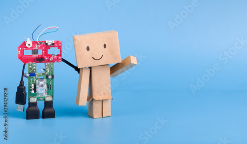 Metal and cardboard robots on blue panorama background Wallpaper Mural