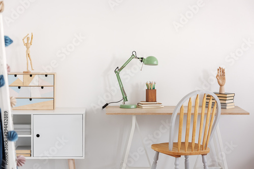 Obraz Pile of books, wooden hand and industrial mint colored lamp on stylish wooden desk in white kid's bedroom - fototapety do salonu