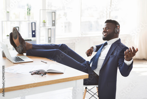 Young relaxed businessman having fun at office - 294433088
