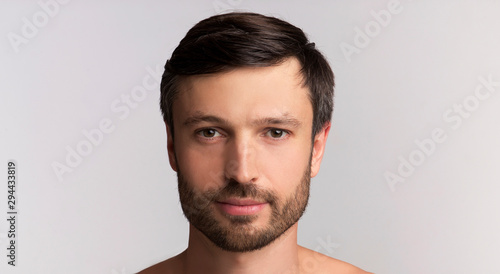 Serious Man Looking At Camera Posing Over White Background, Panorama