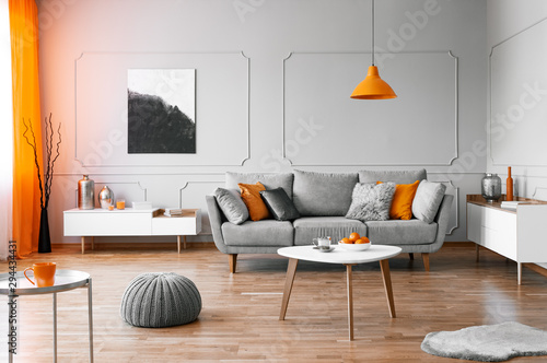 Stylish coffee table with kinck knacks in front of elegant couch with pillows - 294434431