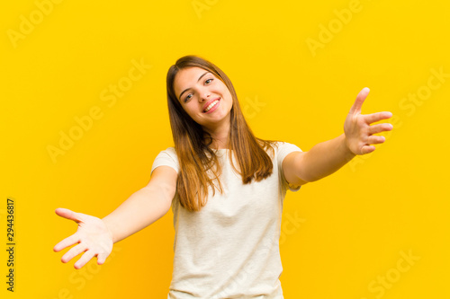 Obraz young pretty woman smiling cheerfully giving a warm, friendly, loving welcome hug, feeling happy and adorable against orange background - fototapety do salonu