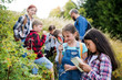 canvas print picture - Group of school children with teacher on field trip in nature, learning science.