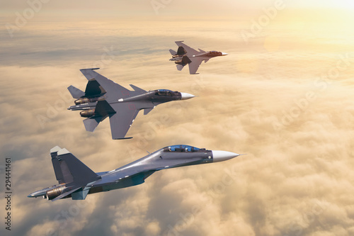 Group of three aircraft fighter jet airplane sun glow flying high in the sky above the clouds.