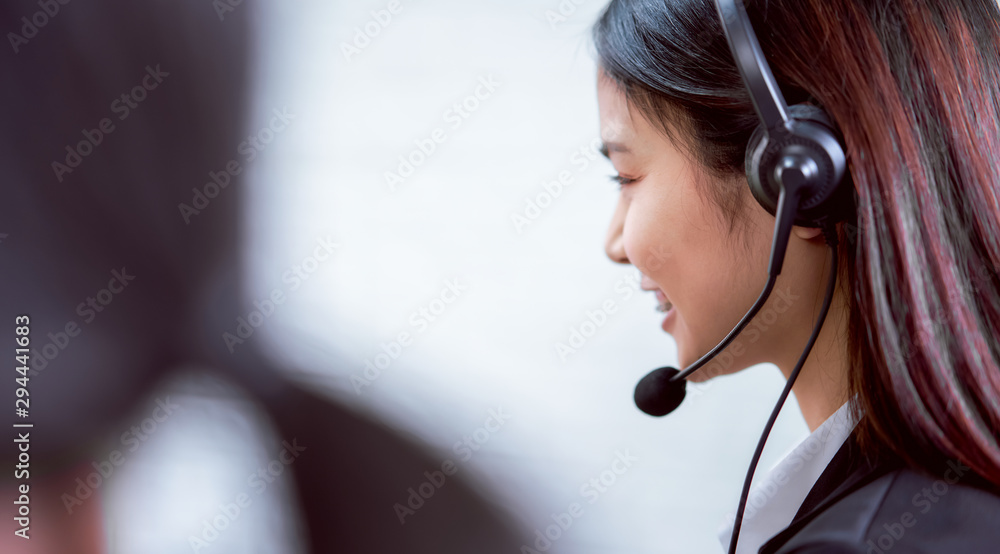 Fototapeta Back view of woman consultant wearing microphone headset of customer support phone operator at workplace.