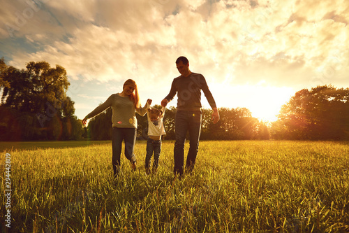 Canvastavla  Happy family walks on the park at sunset.