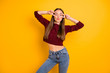 Portrait of lovely woman with eyes closed making v-signs wearing denim jeans burgundy jumper isolated over yellow background