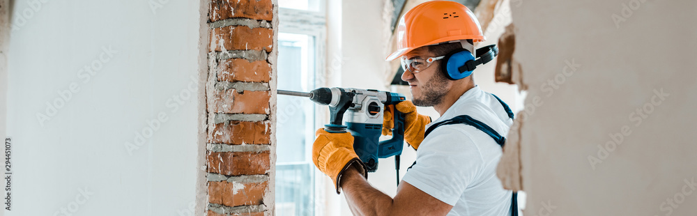 Fototapety, obrazy: panoramic shot of handyman in uniform and yellow gloves using hammer drill
