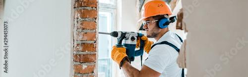 Fotografia, Obraz panoramic shot of handyman in uniform and yellow gloves using hammer drill