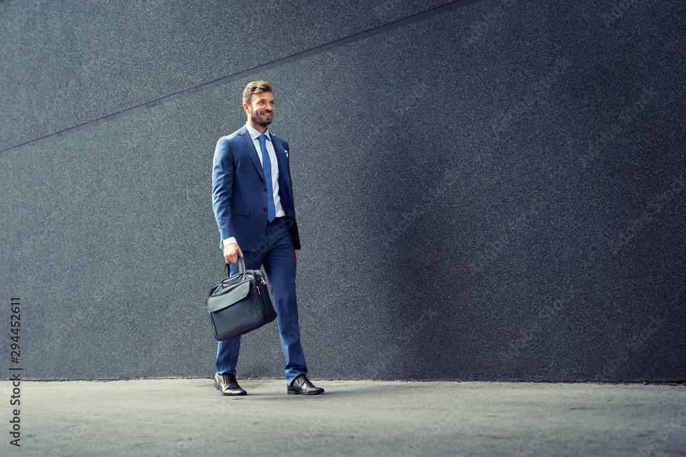 Fototapeta Walking business man with briefcase.
