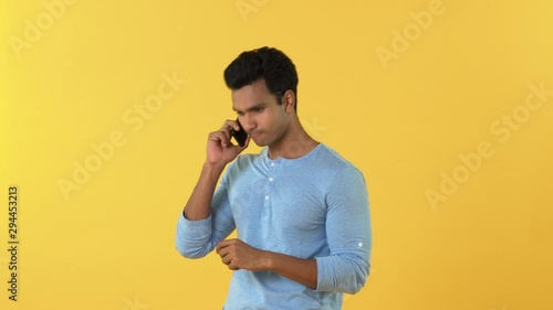 Fotografía  Young smiling Indian man talking on cell phone isolated on yellow studio backgro