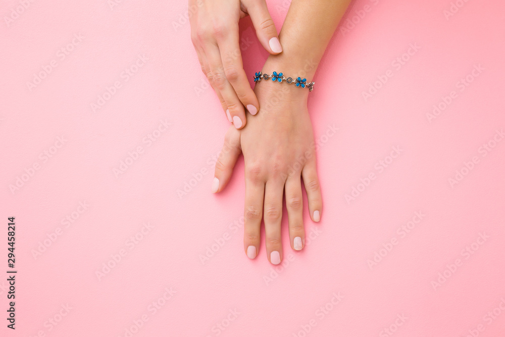 Fototapeta Blue flower bracelet on woman's wrist. Pastel pink background. Care about hand skin and nails. Closeup.