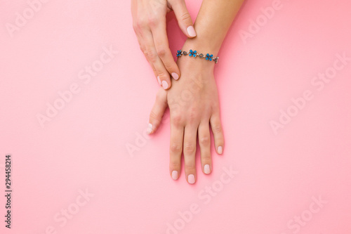 Obraz Blue flower bracelet on woman's wrist. Pastel pink background. Care about hand skin and nails. Closeup. - fototapety do salonu
