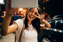 Young Woman Using Smartphone In The City At Night, Taking A Selfie