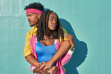 Young Black Lovers Posing In Front Of A Blue Wall