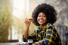 Happy Young Black Woman Eating Cookie