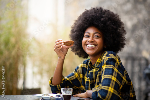 Photo happy young black woman eating cookie