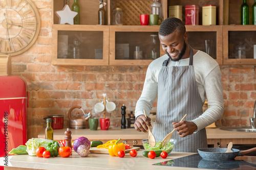 Fotografie, Obraz  Handsome man preparing fresh healthy salad at kitchen