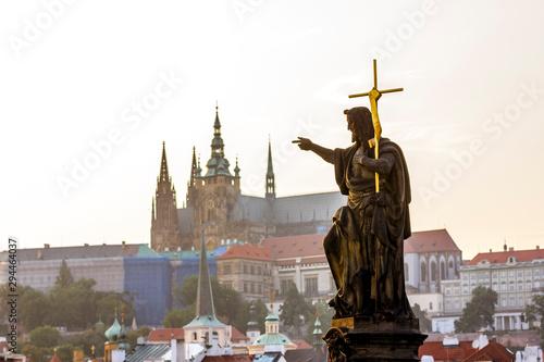 Fotografia Sculpture of John the Baptist on Charles bridge against the Prague castle