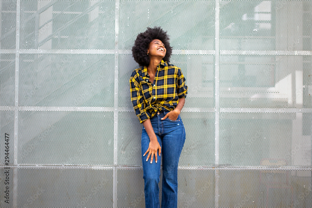 Fototapeta cheerful young black woman laughing and looking up