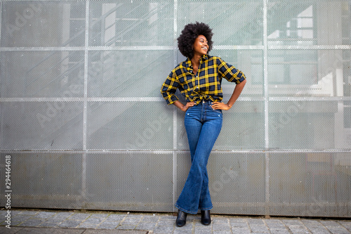 Fototapeta Full body fashionable young african american woman with afro smiling obraz