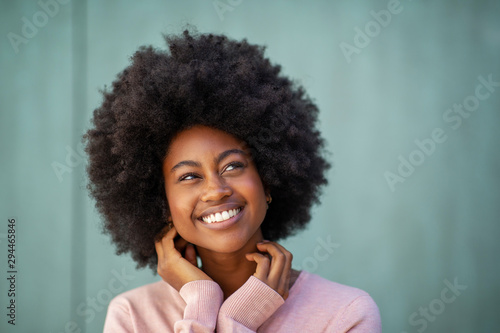 beautiful young black woman smiling with hands by face and looking away