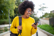 Smiling Young Black Woman With Glasses And Bag Looking At Cellphone Outdoors