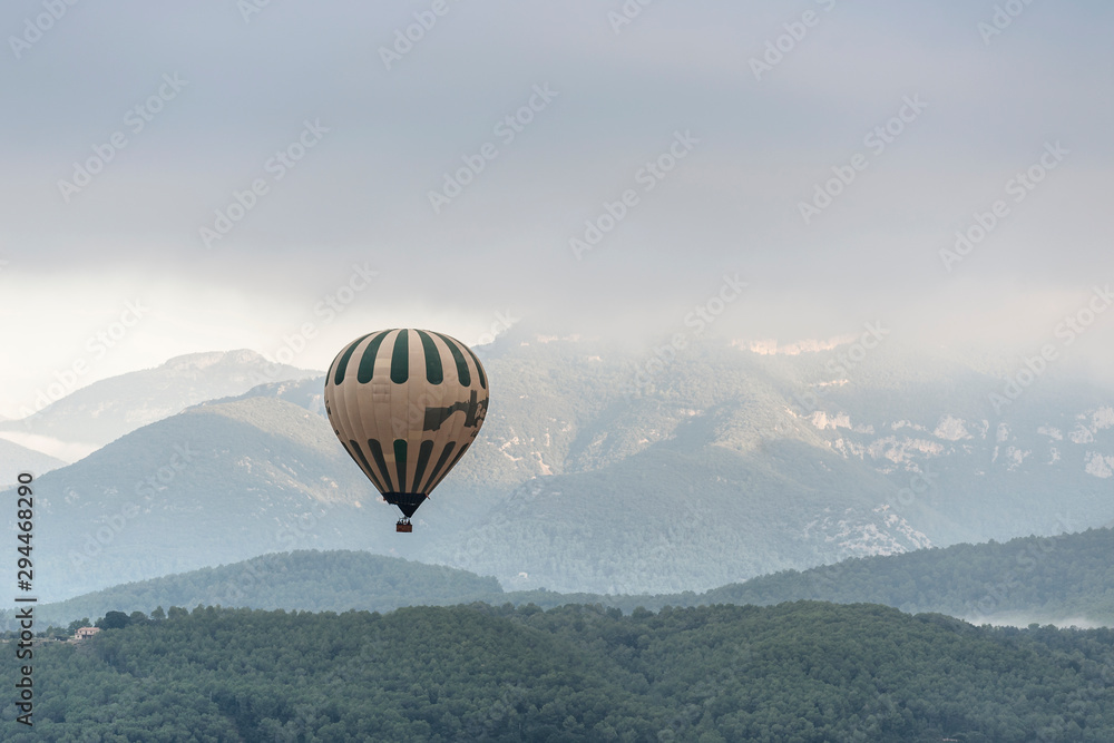 Fototapety, obrazy: A hot air balloon flies over a sea of clouds in the region of La Garrotxa, in Girona (Spain) at dawn.