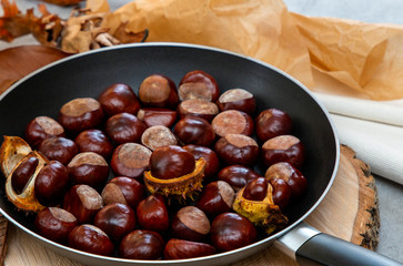 fresh clean shiny chestnuts in a pan with autumn foliage and paper parcels