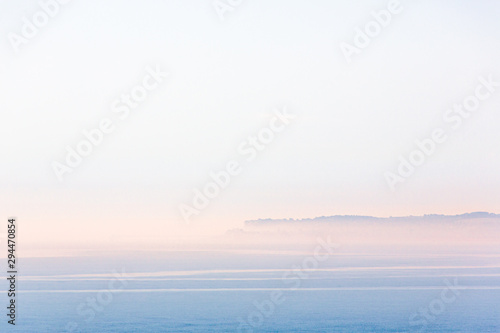 Foto auf Gartenposter Weiß Minimalist landscape scene of Sandwich Bay, Kent on a misty but bright summer morning. The town of Deal peninsular can just be seen through the mist and there is a soft glow of sunrise.