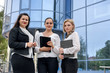 Three business ladies with tablets standing outside building and looking in camera