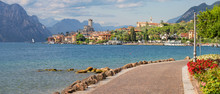 Malcesine - The Promenade Over The Lago Di Garda Lake With The Town And Castle In The Background.