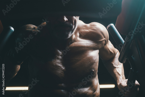 Fotografie, Tablou  Handsome athletic men pumping up muscles push-ups on uneven bars workout fitness