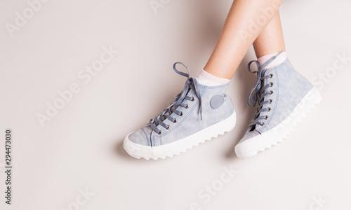 Obraz na płótnie Pastel blue sneakers on crossed legs - casual footwear