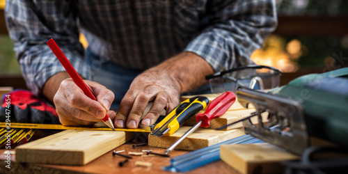 Fotografiet Adult carpenter craftsman with a pencil and the carpenter's square trace the cutting line on a wooden table