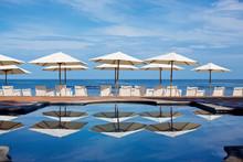 White Beach Umbrellas And Lounge Chairs At Sunny Ocean Poolside, Punta De Mita, Nayarit, Mexico